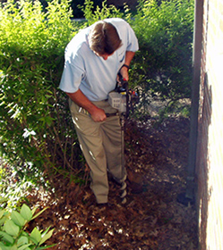 Using a gas-powered auger to install a termite bait station