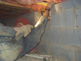 Pulling back insulation in a crawlspace to look for signs of termite activity.