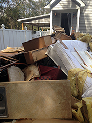 Household furnishings piled outside of flooded house