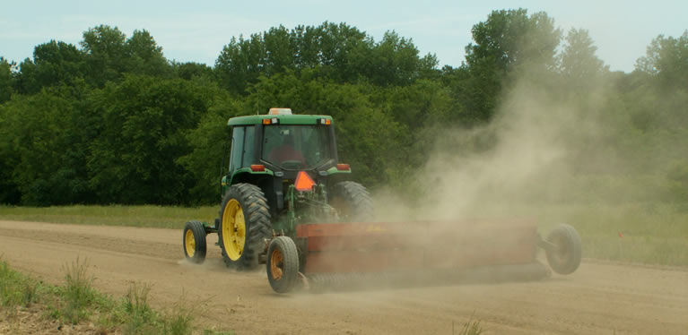 Tractor pulling a cultipacker through a seeded field